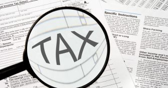 Federal tax forms under a magnifying glass.